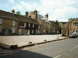 Buildings on the west side of The Square, Blanchland. Photo Northumberland County Council.